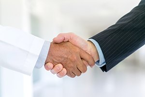 Man in lab coat and man in suit shaking hands