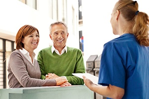 Smiling older couple talks to dental team member