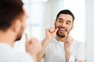 bearded man in white shirt flossing in the mirror