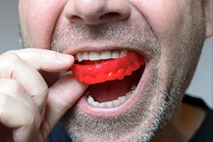 close up of man with facial hair putting in red mouthguard