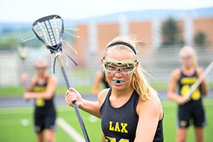 Young girl with mouthguard playing lacrosse