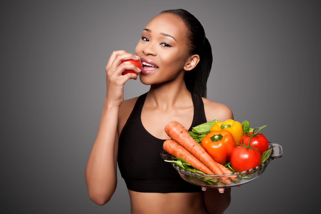 fit woman smiling eating apple