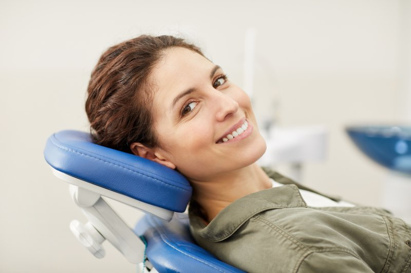 a woman smiling while sitting in the dentist's chair