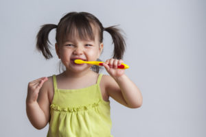 Smiling little girl in pigtails brushing her teeth